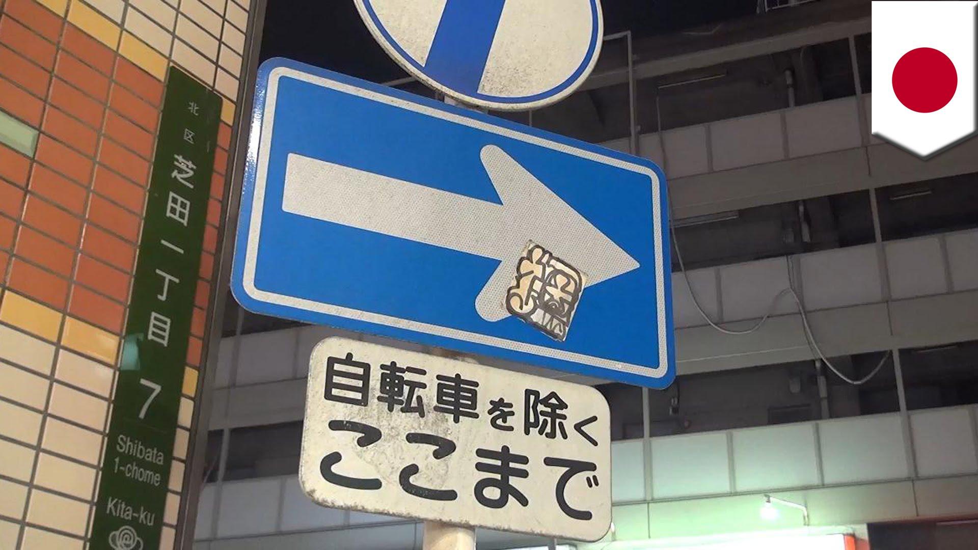 道路標識にシール貼った女